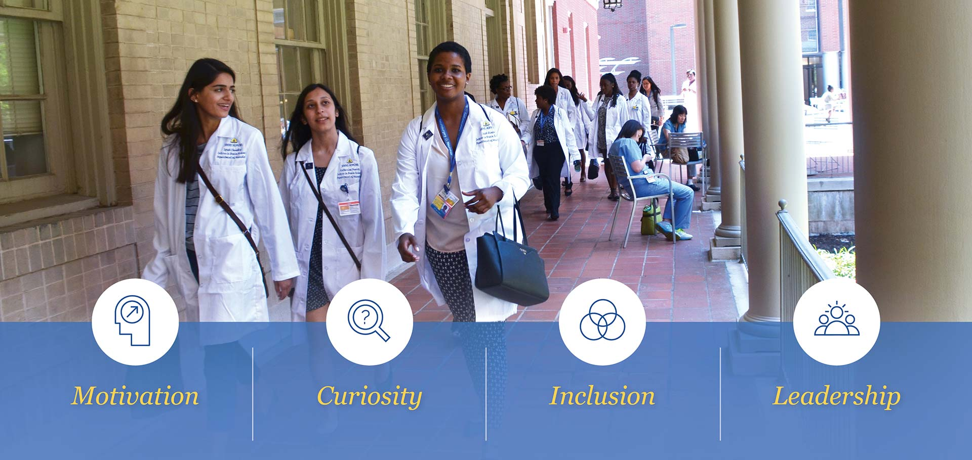 students in white lab coats walking through courtyard